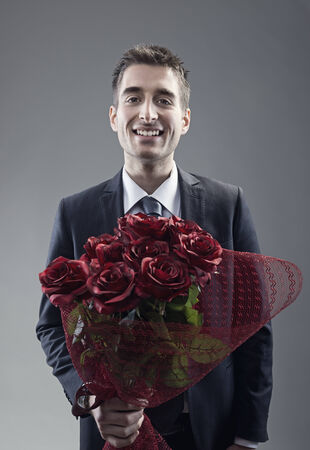 suitor: A handsome suitor holding out large bouquet of red roses  Stock Photo