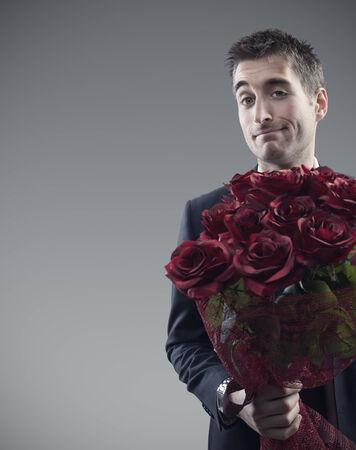 rosas rojas: Hombre que sostiene a gran ramo de rosas rojas Foto de archivo