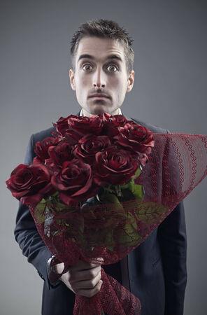 roses rouges: Choqu� homme tendant grand bouquet de roses rouges