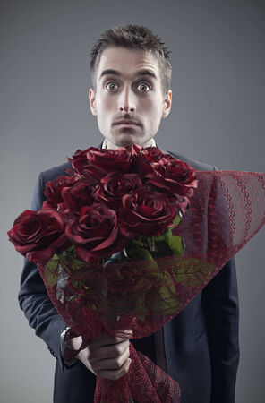 suitor: Shocked man holding out large bouquet of red roses