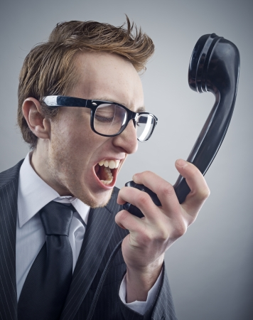 aggressive people: Angry nerd businessman retro telephone call shouting Stock Photo