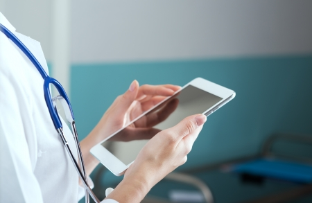 Close up of a female doctor in scrubs using digital tablet. photo