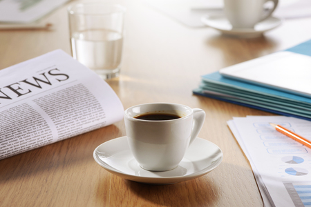 Business Office scene, Coffee, newspaper, water glass on meeting desk photo