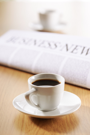 Two cup of coffee and newspaper on wooden desk photo