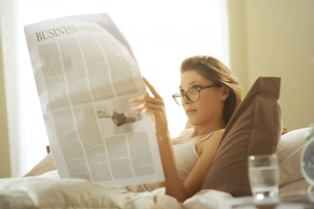 Young woman lying on the bed at home and reading the newspaper  photo