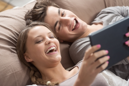 Happy young couple lying on the bed in a bedroom and using digital tablet. photo