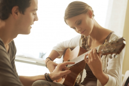playing the guitar: Young beautiful couple resting at home and playing guitar