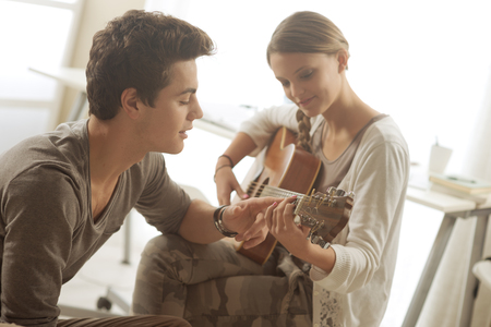 teaching music: Young beautiful couple resting at home and playing guitar