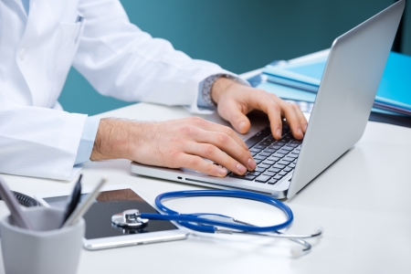 Doctor working at his desk with stethoscope, laptop and tablet. photo