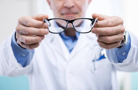oculist: Oculista dando un par de gafas durante una visita.