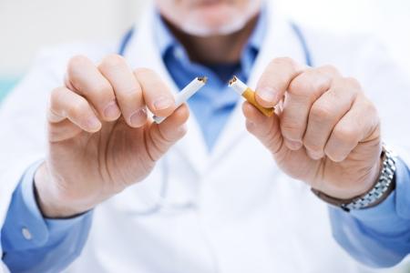 hombre fumando: Doctor mayor que rompe un cigarrillo, dejar de fumar concepto.