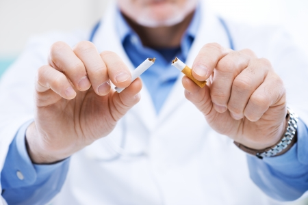 unhealthy living: Senior doctor breaking a cigarette, stop smoking concept.