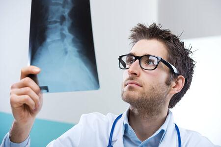 columna vertebral humana: Radi�logo Profesional examinar una imagen de rayos X de la columna vertebral humana. Foto de archivo