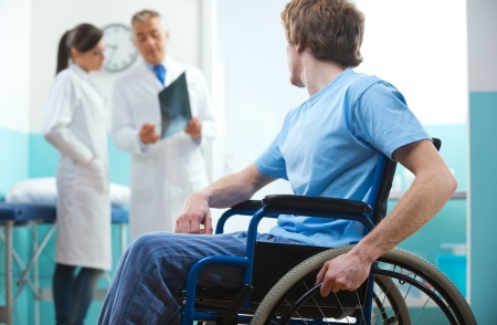 Young patient in wheelchair with doctors in the background.