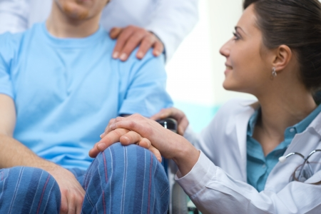 impairment: Young female doctor comforting a young patient on wheelchair. Stock Photo