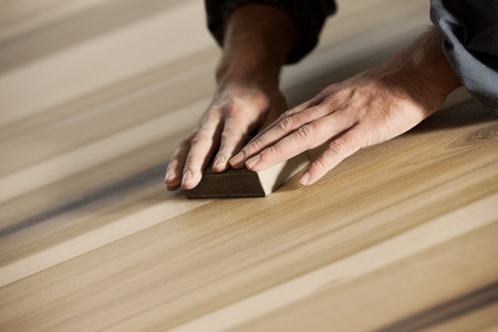 refinish: Professional carpenter sanding and refinishing wood surface.