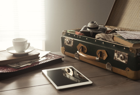 Travelers suitcase with vintage items, tablet and a cup of coffee.