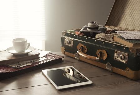 travel: Walizka podróżnika z rocznika elementów, tabletki i filiżanką kawy.