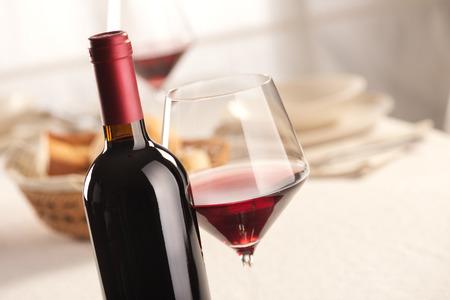 merlot: Red wine glass and bottle still life at restaurant.