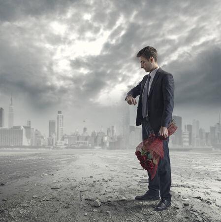 futuristic man: Elegant man waiting for a date with red roses on futuristic metropolitan background. Stock Photo