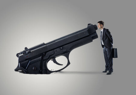 tiptoe: Young Businessman looking into a gun barrel. Stock Photo