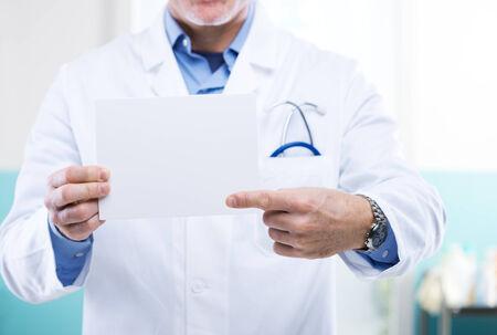 bata de laboratorio: Doctor que señala en un pequeño cartel blanco, se puede agregar un mensaje.