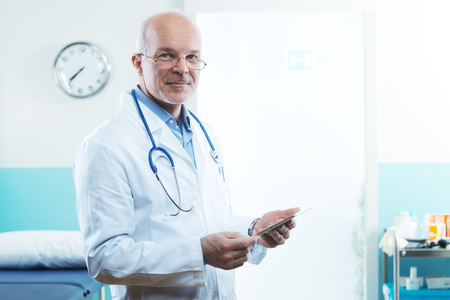 doctors tools: Senior doctor with tablet and medical equipment in the background. Stock Photo