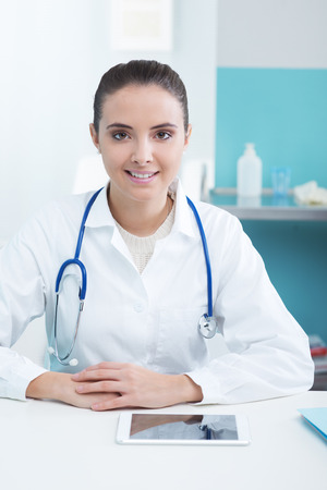 Portrait of a beautiful young female doctor in office photo