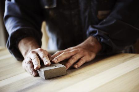 Professional carpenter sanding and refinishing wood surface. Stock Photo