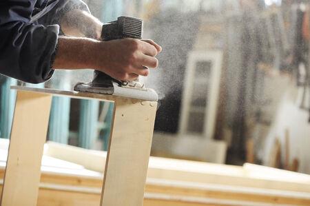 menuisier: Carpenter travaille sur un meuble avec une raboteuse. Banque d'images