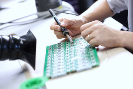 worktable: Technician assembling electonic components at his worktable.