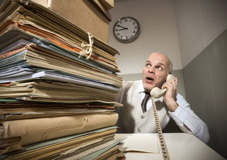 overwork: Vintage senior businessman on the phone with a huge stack of files.