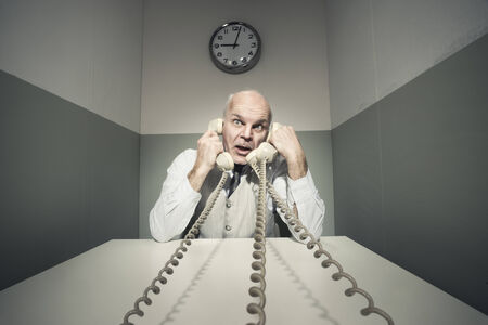 overburdened: Stressed overworked businessman talking on the phone, vintage setting. Stock Photo