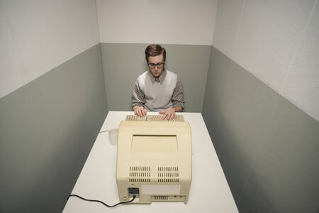small room: Vintage nerd guy working on old computer in a small room.