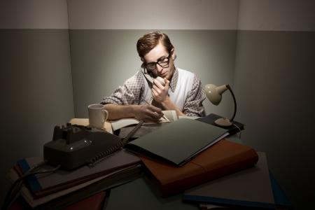 messy desk: Friki retro en el tel�fono con escritorio desordenado en una habitaci�n peque�a.