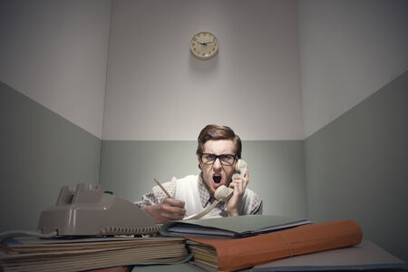 messy desk: Angry nerd guy at the phone with messy desk. Stock Photo