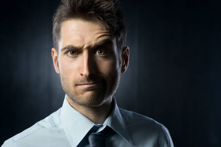 eyebrow raised: Young businessman: confused expression with raised eyebrow. Stock Photo