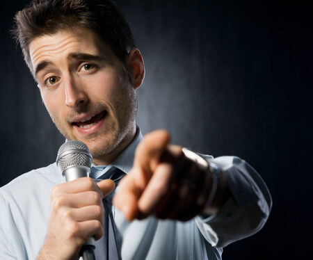 Man giving a speech with microphone and gesturing. photo