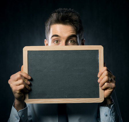 Young handsome man with raised eyebrows holding a blackboard. photo