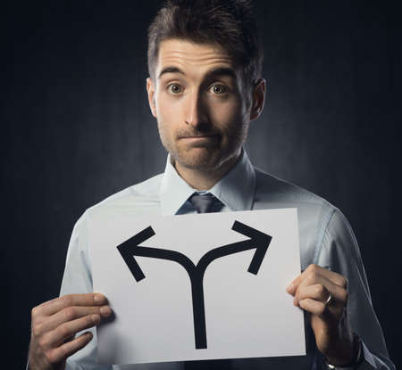 deciding: Man holding a sign with directions and pensive expression.