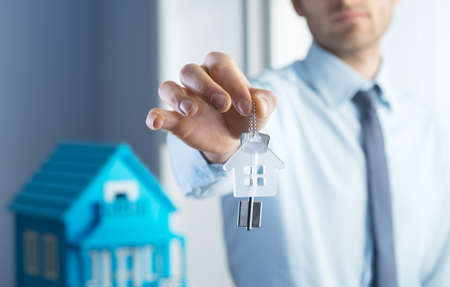 one young man: Real estate agent giving house keys with model house on background. Stock Photo