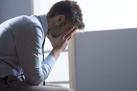 distraught: Pensive tired businessman  with head in hands. Stock Photo