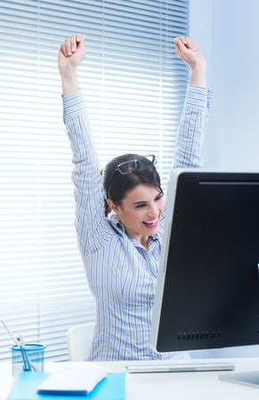 good news: Young joyful woman at desk with fists raised receiving good news.