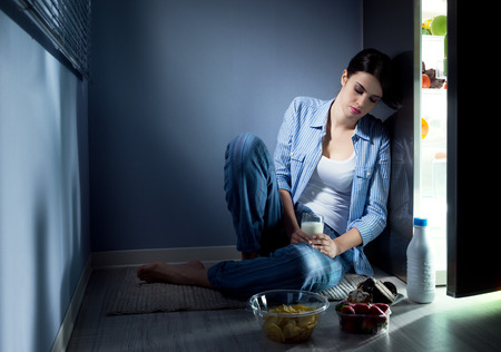 Sleepless sad woman sitting on kitchen floor having a glass of milk. photo