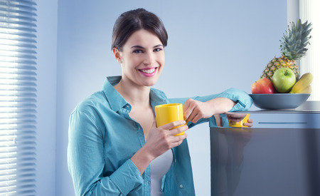 Young cheerful woman holding a yellow mug and leaning against refrigerator. photo