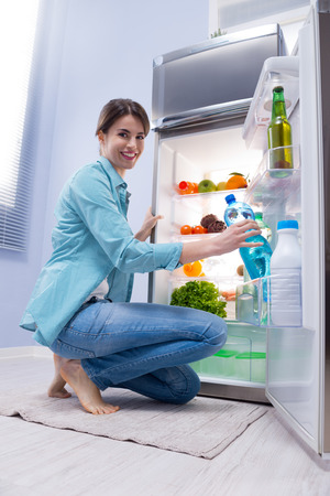 freezer: Young woman taking a water bottle from refrigerator and smiling at camera. Stock Photo