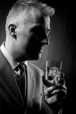 whisky: Businessman holding a glass of whisky on dark background