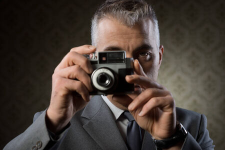 studio photography: Handsome photographer shooting with vintage camera against retro wallpaper. Stock Photo