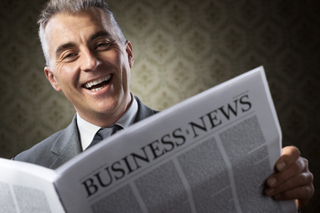 Handsome businessman reading news against vintage wallpaper background. photo