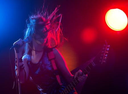 Jonge tiener rockster zingen en elektrische gitaar spelen op het podium. Stockfoto